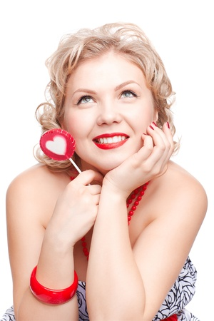 isolated portrait of beautiful smiling young blonde size plus woman model with red lollipop with white heart middle photo