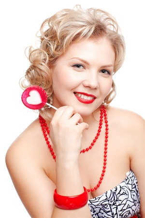 isolated portrait of beautiful young happy blonde size plus woman model with red lollipop with white heart middle photo