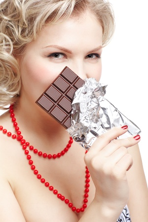 size: isolated portrait of beautiful young blonde size plus woman model hiding part of her face behind bar of chocolate in foil