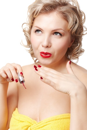 isolated portrait of beautiful young blonde size plus woman model blowing on her manicured fingers to dry nail polish photo