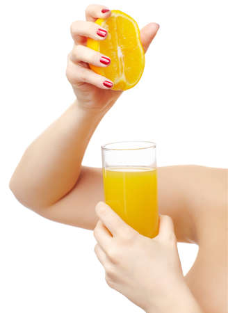 isolated body part portrait of beautiful young womans manicured hands squeezing out half of orange into the glass with orange juice photo