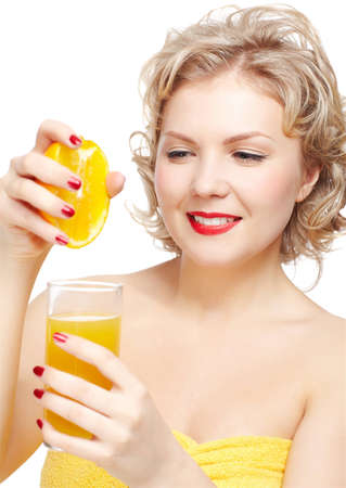 isolated portrait of beautiful young blonde size plus woman model in yellow bath towel pressing out half of orange into the glass with orange juice photo