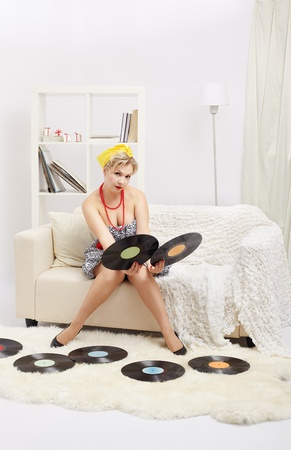 indoor portrait of beautiful young blonde size plus woman model sitting on sofa choicing one of two vinyl records in hands photo
