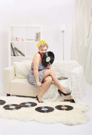 indoor portrait of beautiful young blonde size plus woman model sitting on sofa with vinyl records in interior photo