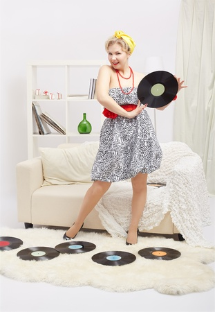 indoor portrait of beautiful young blonde size plus woman model standing on fur carpet with vinyl records in interior photo