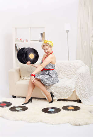 indoor portrait of beautiful happy young blonde size plus woman model sitting on sofa with vinyl records in hands photo