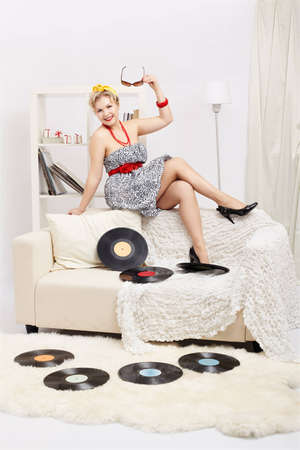 indoor portrait of beautiful happy young blonde size plus woman model sitting on sofa with vinyl records in interior photo
