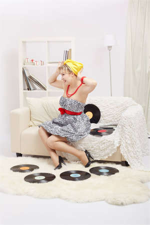 indoor portrait of beautiful smiling young blonde size plus woman model sitting on sofa with vinyl records in interior photo