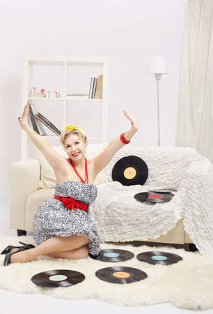 indoor portrait of beautiful young happy blonde size plus woman model sitting on fur carpet with vinyl records around in interior photo
