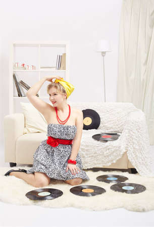 indoor portrait of beautiful smiling young blonde size plus woman model sitting on fur carpet with vinyl records around in interior photo