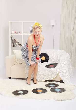 indoor portrait of beautiful young blonde size plus woman model standing on fur carpet with vinyl records around in interior photo