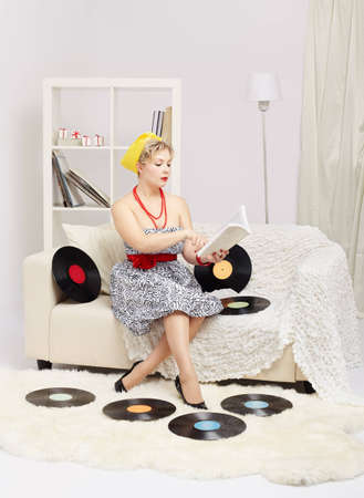 indoor portrait of beautiful young blonde size plus woman model sitting on sofa with vinyl records around and reading book photo