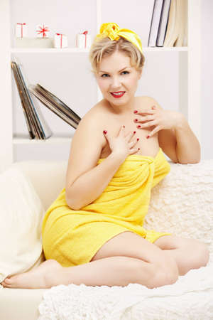 interior portrait of beautiful young blonde size plus woman model in yellow bath towel sitting on sofa Stock Photo