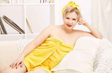 interior portrait of beautiful young blonde size plus woman model in yellow bath towel sitting on sofa photo