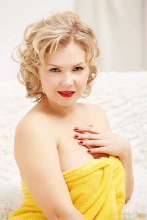 portrait of beautiful young blonde size plus woman model in yellow bath towel photo