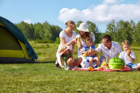 familia picnic: retrato de grupo al aire libre de la familia feliz con pic-nic sobre la hierba verde en el parque Foto de archivo