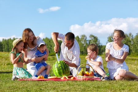 outdoor group portrait of happy family having picnic on green grass in park  father is cutting watermelon  photo