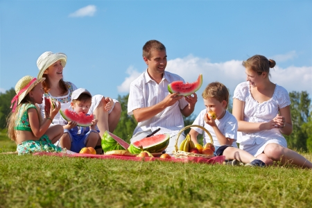 family picnic: outdoor group portrait of happy family having picnic on green grass in park and enjoying watermelon