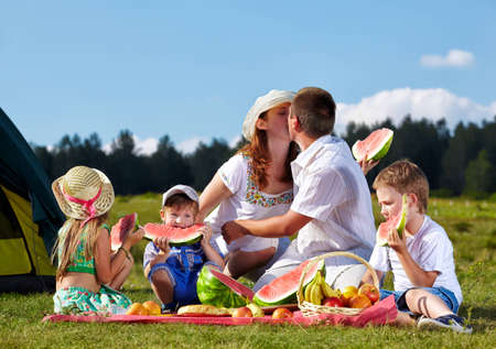 outdoor group portrait of happy family having picnic on green grass in park and enjoying watermelon photo