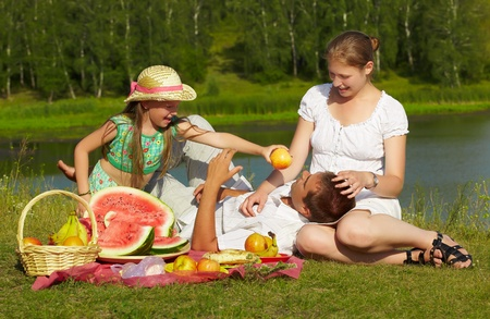 family picnic: outdoor group portrait of happy family having picnic on green grass in park