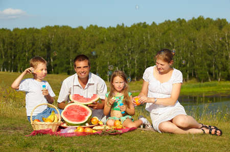 outdoor group portrait of happy family having picnic on green grass in park and enjoying fruits photo