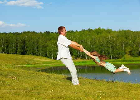 rotate: outdoor portrait of happy father holding his daughter