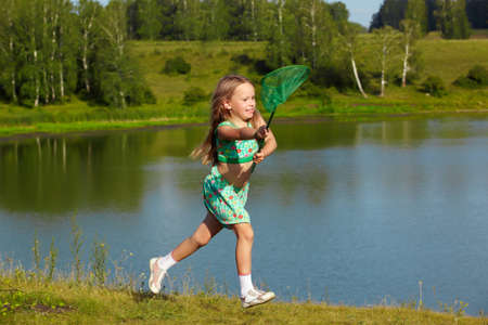 outdoor portrait of little girl running with butterfly net along the bank of the pond photo