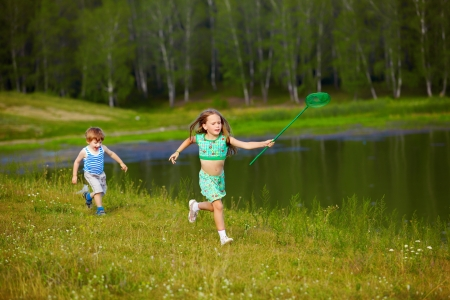 outdoor portrait of little kids running with butterfly net along the bank of the pond photo