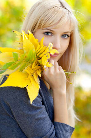 Young woman with a bouquet of leaves on a background of autumn park photo