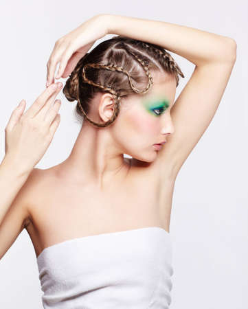 sideview portrait of beautiful young dark blonde woman with creative braid hairdo posing on gray with hands over head Stock Photo - 12671385