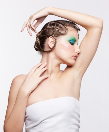 portrait of beautiful young dark blonde woman with creative braid hairdo and green eye shades touching her neck photo