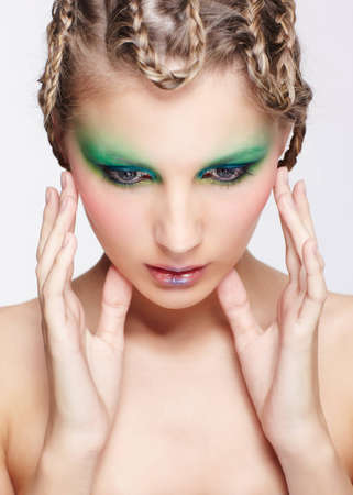 portrait of beautiful young dark blonde woman with creative braid hairdo and green eye shades touching her face photo