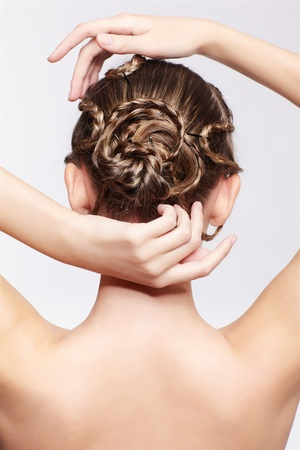 back view portrait of beautiful young dark blonde woman with creative plait hairdo on gray Stock Photo