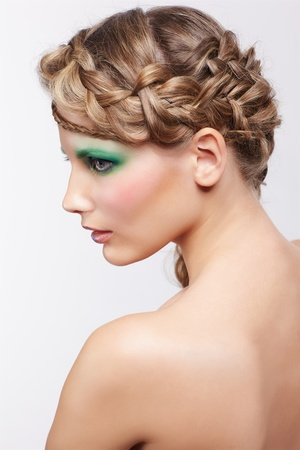 portrait of beautiful young dark blonde woman with creative plait hairdo and green eye shades make up on gray