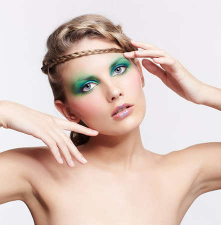 portrait of beautiful young dark blonde woman with creative braid hairdo and green eye shades make up on gray photo