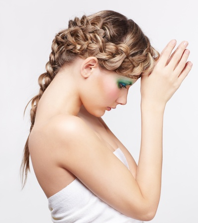 sideview portrait of beautiful young dark blonde woman with creative plait hairdo posing on gray Stock Photo