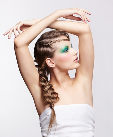 portrait of beautiful young dark blonde woman with creative braid hairdo posing on gray putting hands over her head photo