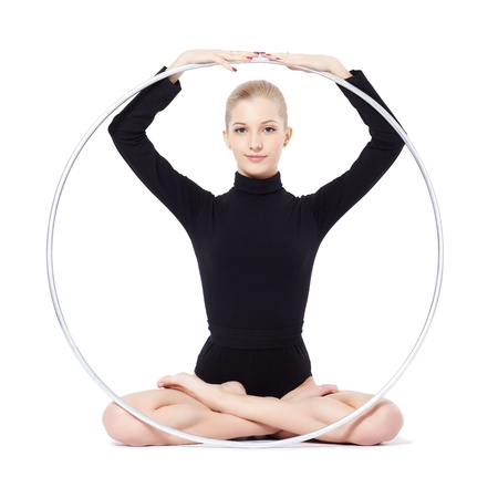 hula: isolated portrait of beautiful young blonde woman gymnast sitting lotus pose with hula hoop