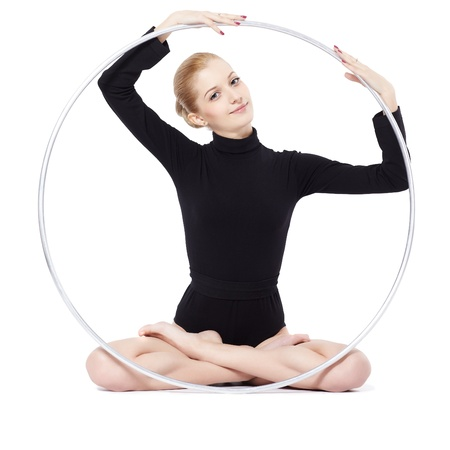 isolated portrait of beautiful young blonde woman gymnast training yoga exercise lotus pose with hula hoop photo