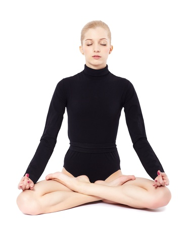 isolated portrait of beautiful young blonde woman gymnast sitting in lotus pose with eyes closed photo