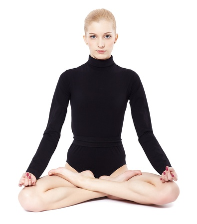 lotus pose: isolated portrait of beautiful young blonde woman gymnast sitting in lotus pose Stock Photo
