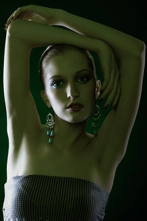 green tinted portrait of beautiful young blonde woman in ear-rings with hands over her head photo