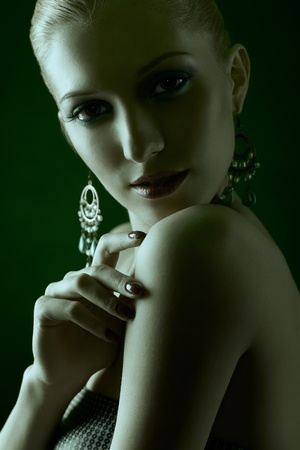 green toned portrait of beautiful young blonde woman in ear-rings touching her shoulder with manicured fingers photo