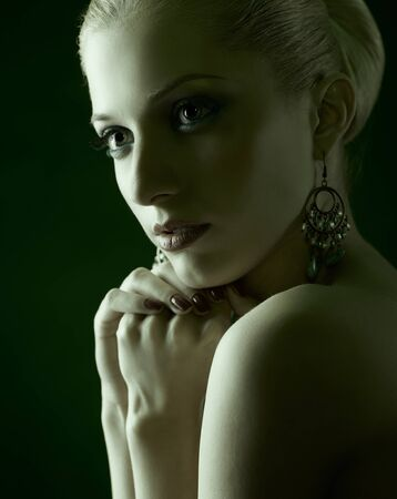 green toned portrait of beautiful young blonde woman in jewelry photo