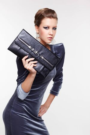 portrait of beautiful young brunette woman in fancy dress with clutch on gray Stock Photo - 13208645