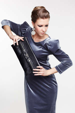 portrait of beautiful young brunette woman in fancy dress holding clutch in hands on gray Stock Photo - 13208640