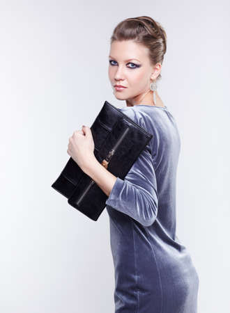 portrait of beautiful young brunette woman in stylish dress with clutch in hand on gray photo