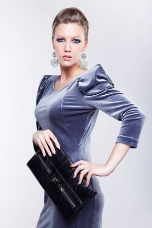 portrait of beautiful young brunette woman in stylish dress with clutch in hands on gray Stock Photo - 13208659