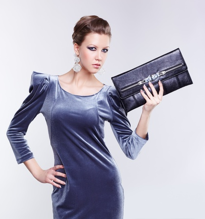 portrait of beautiful young brunette woman in stylish dress holding clutch in hand Stock Photo - 13208636