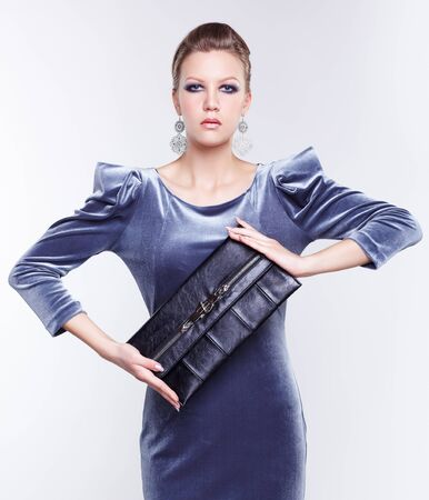 portrait of beautiful young brunette woman in stylish dress holding clutch with both hands on gray Stock Photo - 13208638
